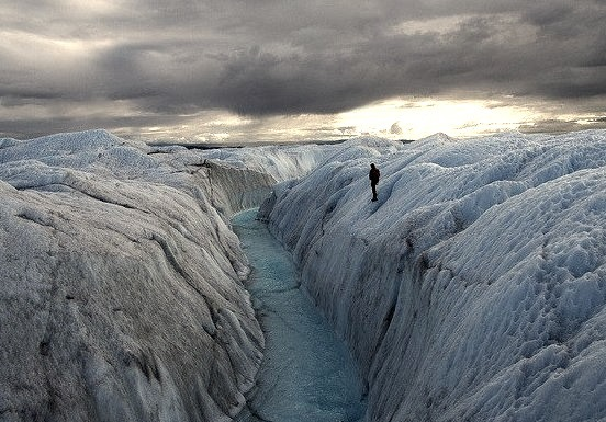 A supraglacial meltwater stream cuts a canyon through the surface of the Greenland ice sheet